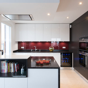 Photo of a large contemporary u-shaped open plan kitchen in Paris with white cabinets, red splashback, an undermount sink, flat-panel cabinets, glass sheet splashback, a peninsula, ceramic floors and panelled appliances.