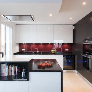 Modern inredning av ett stort kök, med vita skåp, rött stänkskydd, en undermonterad diskho, släta luckor, glaspanel som stänkskydd, en halv köksö, klinkergolv i keramik och integrerade vitvaror