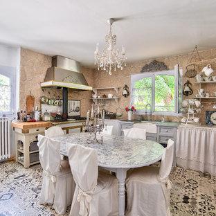 Cette photo montre une cuisine américaine romantique avec un évier de ferme et un sol multicolore.