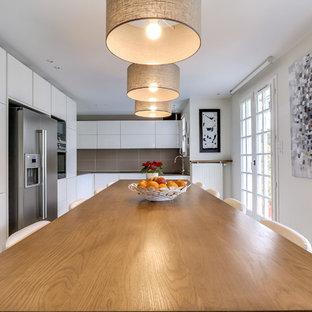 Exemple d'une grande cuisine américaine tendance en L avec un placard à porte plane, des portes de placard blanches, une crédence grise et un électroménager en acier inoxydable.