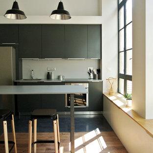 Exemple d'une cuisine américaine linéaire tendance de taille moyenne avec un placard à porte plane, des portes de placard noires, un électroménager en acier inoxydable, un sol en bois brun, un îlot central et une crédence grise.