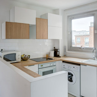 Small scandinavian u-shaped open plan kitchen in Paris with a drop-in sink, white cabinets, wood benchtops, white splashback, subway tile splashback, white appliances, no island, flat-panel cabinets, ceramic floors, grey floor and beige benchtop.