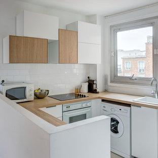 Modelo de cocina en U, escandinava, pequeña, abierta, sin isla, con fregadero encastrado, puertas de armario blancas, encimera de madera, salpicadero blanco, salpicadero de azulejos tipo metro y electrodomésticos blancos