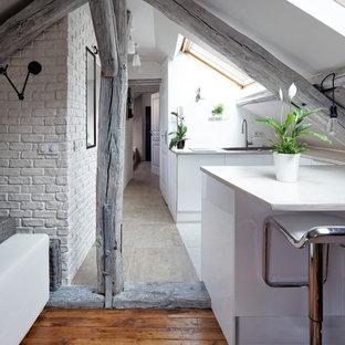 Idée de décoration pour une petite cuisine ouverte design en U avec un placard à porte plane, des portes de placard blanches et une péninsule.