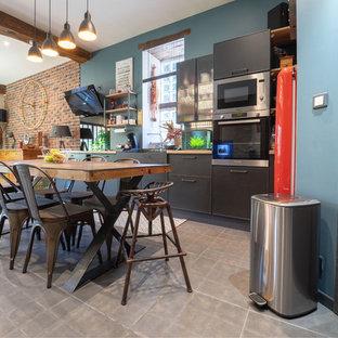 Inspiration pour une cuisine ouverte linéaire urbaine avec un évier de ferme, un placard à porte plane, des portes de placard noires, un plan de travail en bois, un électroménager en acier inoxydable, aucun îlot, un sol gris et un plan de travail marron.