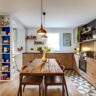 Cette image montre une cuisine américaine bohème en L avec un évier encastré, un placard à porte plane, des portes de placard en bois brun, une crédence noire, un électroménager encastrable et aucun îlot.