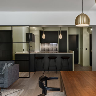 This is an example of a small contemporary u-shaped eat-in kitchen in Paris with an integrated sink, flat-panel cabinets, black cabinets, quartzite benchtops, white splashback, cement tile splashback, panelled appliances and a peninsula.
