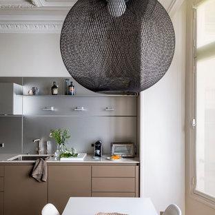 Aménagement d'une cuisine américaine linéaire contemporaine de taille moyenne avec un évier 1 bac, un sol en bois brun, une crédence métallisée et aucun îlot.