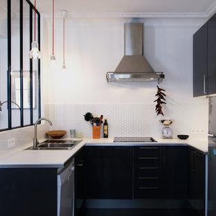 Cette photo montre une cuisine scandinave en U de taille moyenne et fermée avec un placard à porte plane, une crédence blanche, aucun îlot, un évier posé, des portes de placard noires et un électroménager encastrable.