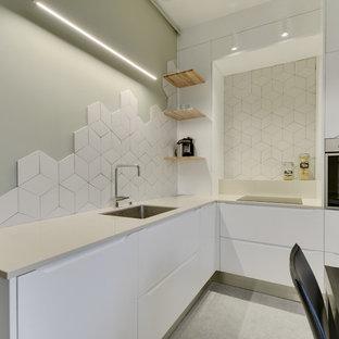 Aménagement d'une cuisine moderne en L fermée et de taille moyenne avec des portes de placard blanches, un plan de travail en quartz, une crédence blanche, une crédence en carreau de céramique, un électroménager encastrable, un sol en linoléum, aucun îlot, un sol gris, un plan de travail beige, un évier encastré et un placard à porte plane.