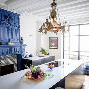 Exemple d'une cuisine parallèle chic avec un évier encastré, un placard à porte plane, des portes de placard noires, une crédence blanche, un sol en bois brun, un îlot central, un sol marron et un plan de travail blanc.