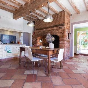 Idées déco pour une grand cuisine ouverte linéaire campagne avec un placard à porte plane, des portes de placard blanches, une crédence beige, un sol en carreau de terre cuite et un îlot central.