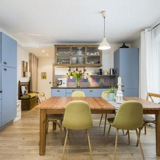 Cette photo montre une cuisine éclectique en L avec un placard à porte plane, des portes de placard bleues, une crédence multicolore, un électroménager encastrable, un sol en bois clair, un îlot central, un sol beige et un plan de travail gris.
