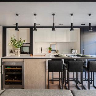 Cette photo montre une cuisine tendance en L avec un évier encastré, un placard à porte plane, des portes de placard en bois clair, une crédence blanche, un électroménager en acier inoxydable, un sol en bois brun, un îlot central, un sol marron et un plan de travail blanc.