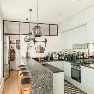 Inspiration pour une cuisine design en U fermée avec un placard à porte plane, des portes de placard blanches, une crédence en carreau de miroir, un électroménager noir et un sol multicolore.