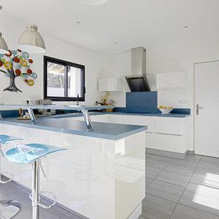 Cette photo montre une cuisine tendance en U avec un placard à porte plane, des portes de placard blanches, un électroménager en acier inoxydable, une péninsule et un sol gris.