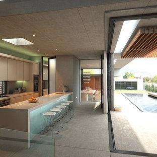 Inspiration pour une grande cuisine américaine parallèle design avec des portes de placard beiges et une péninsule.