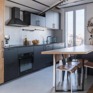 Idée de décoration pour une cuisine ouverte parallèle design de taille moyenne avec un évier intégré, un placard à porte plane, des portes de placard noires, une crédence grise, un électroménager noir, un sol en carrelage de porcelaine, une péninsule, un sol gris et un plan de travail noir.