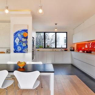 Idées déco pour une grande cuisine américaine contemporaine en L avec un placard à porte plane, des portes de placard blanches, un électroménager en acier inoxydable et aucun îlot.