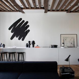 Idée de décoration pour une cuisine ouverte linéaire design avec une crédence blanche, un sol en bois brun, un sol marron, un plan de travail blanc, un évier encastré, un placard à porte plane, aucun îlot, un plafond à caissons et un plafond en poutres apparentes.