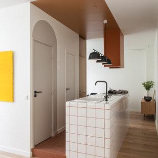 Nordische Küche mit Einbauwaschbecken, Arbeitsplatte aus Fliesen, hellem Holzboden, Kücheninsel, beigem Boden und weißer Arbeitsplatte in Paris