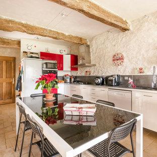 Cette image montre une cuisine américaine méditerranéenne en L avec un évier 2 bacs, un placard à porte plane, des portes de placard blanches, une crédence grise, un électroménager blanc, un sol beige et un plan de travail gris.