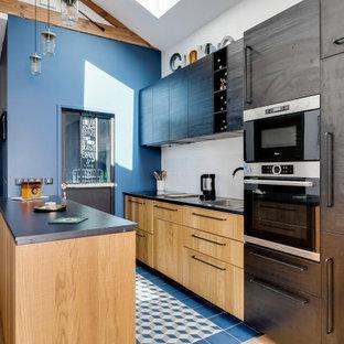 Idées déco pour une cuisine parallèle industrielle avec un évier posé, un placard à porte plane, des portes de placard en bois clair, un électroménager en acier inoxydable, une péninsule, un sol bleu et un plan de travail noir.