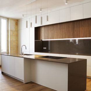 Design ideas for an expansive contemporary galley open plan kitchen in Bordeaux with an undermount sink, beaded inset cabinets, white cabinets, quartz benchtops, brown splashback, panelled appliances, light hardwood floors, with island, brown floor and brown benchtop.