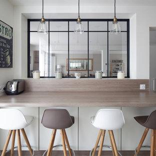 Cette image montre une grand cuisine parallèle urbaine fermée avec un placard à porte plane, des portes de placard blanches, un plan de travail en stratifié, un électroménager encastrable et aucun îlot.