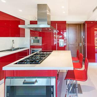 Cette image montre une cuisine design en U fermée avec un évier 2 bacs, un placard à porte plane, des portes de placard rouges, un électroménager en acier inoxydable, un îlot central et un sol blanc.