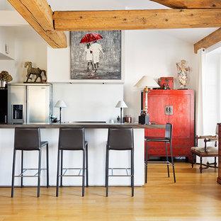 Cette image montre une cuisine bohème avec un électroménager en acier inoxydable, un sol en bois clair, une péninsule et un sol beige.