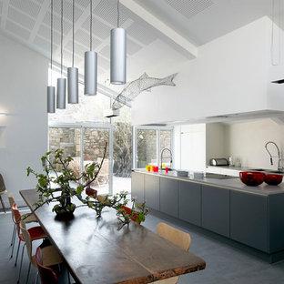 Cette photo montre une grande cuisine américaine parallèle tendance avec un évier 2 bacs, un placard à porte plane, des portes de placard blanches et un îlot central.