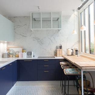 Inspiration pour une cuisine américaine design en U avec un évier encastré, un placard à porte plane, des portes de placard bleues, une crédence blanche et un sol blanc.