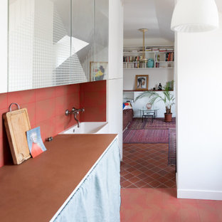 Photo of a contemporary single-wall open plan kitchen in Paris with a farmhouse sink, tile benchtops, red splashback, terra-cotta splashback, ceramic floors, red floor and pink benchtop.