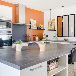 Cette photo montre une cuisine industrielle en L avec un placard à porte plane, des portes de placard blanches, un sol en bois clair, un îlot central, un sol beige et un plan de travail gris.