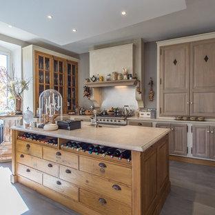 Idées déco pour une cuisine campagne avec un évier 1 bac, un plan de travail en marbre, un îlot central, un placard avec porte à panneau surélevé, des portes de placard en bois brun, un sol gris et un plan de travail beige.