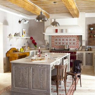Aménagement d'une cuisine américaine méditerranéenne en L de taille moyenne avec un placard avec porte à panneau surélevé, des portes de placard grises, une crédence multicolore, un électroménager en acier inoxydable et un îlot central.