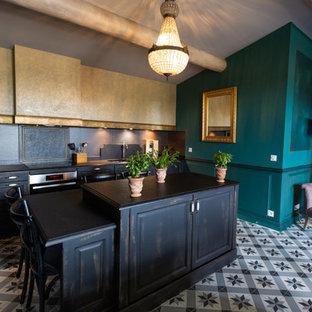 Aménagement d'une cuisine linéaire éclectique avec un placard avec porte à panneau surélevé, des portes de placard en bois vieilli, une crédence noire, un îlot central, un sol multicolore et un plan de travail noir.