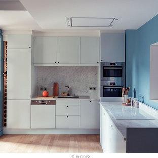 パリの中サイズのモダンスタイルのおしゃれなキッチン (アンダーカウンターシンク、インセット扉のキャビネット、青いキャビネット、大理石カウンター、白いキッチンパネル、大理石の床、シルバーの調理設備の、淡色無垢フローリング、ベージュの床、白いキッチンカウンター) の写真