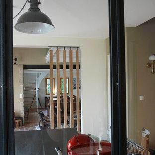 レンヌの大きいインダストリアルスタイルのおしゃれなキッチン (インセット扉のキャビネット、ベージュのキャビネット、ラミネートカウンター、黒いキッチンパネル、テラコッタタイルの床、赤い床) の写真
