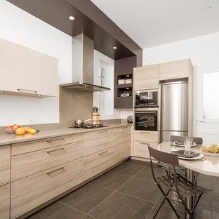 Idées déco pour une grande cuisine américaine contemporaine en L avec un évier encastré, un placard à porte plane, des portes de placard en bois clair et un électroménager en acier inoxydable.