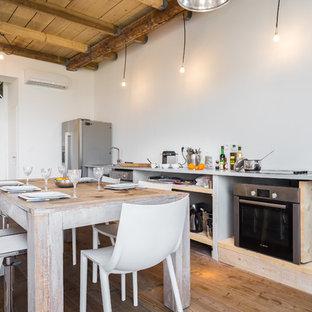 Cette photo montre une cuisine américaine linéaire nature de taille moyenne avec un placard sans porte, un électroménager en acier inoxydable, un sol en bois brun et aucun îlot.