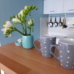 パリの小さいコンテンポラリースタイルのおしゃれなキッチン (シングルシンク、フラットパネル扉のキャビネット、白いキャビネット、木材カウンター、パネルと同色の調理設備、クッションフロア) の写真