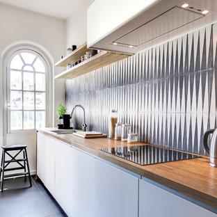 Exemple d'une cuisine linéaire tendance fermée et de taille moyenne avec un placard à porte plane, des portes de placard blanches, un plan de travail en bois, une crédence multicolore et aucun îlot.