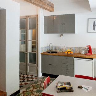 Cette image montre une cuisine américaine linéaire rustique de taille moyenne avec des portes de placard grises, aucun îlot et un plan de travail en bois.