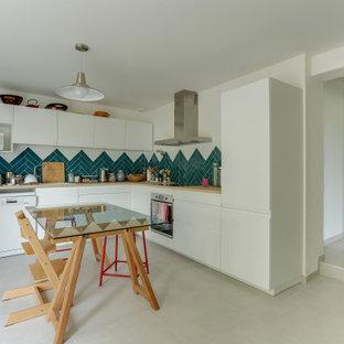 Idée de décoration pour une petite cuisine américaine nordique en L avec un sol en carrelage de céramique, un placard à porte plane, des portes de placard blanches, un plan de travail en bois, une crédence bleue, une crédence en carreau de céramique, un électroménager en acier inoxydable, un plan de travail beige, aucun îlot et un sol gris.