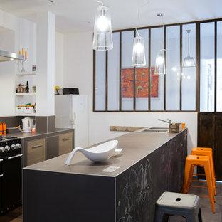 Réalisation d'une cuisine ouverte urbaine de taille moyenne avec des portes de placard en bois brun, une crédence marron, un sol en carrelage de céramique, une péninsule, un évier 2 bacs et un électroménager noir.