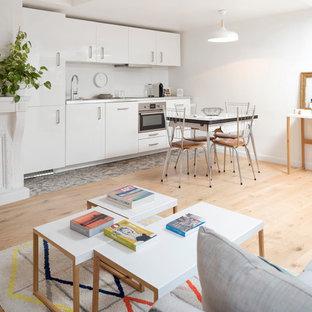 Cette photo montre une cuisine ouverte linéaire scandinave de taille moyenne avec un évier encastré, un placard à porte affleurante, des portes de placard blanches, un plan de travail en inox, un électroménager en acier inoxydable, aucun îlot et un plan de travail gris.