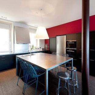 Aménagement d'une grand cuisine américaine linéaire contemporaine avec des portes de placard noires et un îlot central.