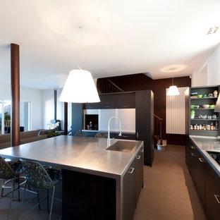 Réalisation d'une grand cuisine ouverte design en U avec un évier intégré, un placard à porte plane, des portes de placard noires, moquette et un îlot central.